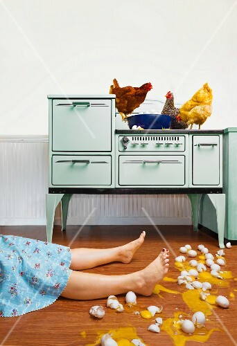 Caucasian woman on kitchen floor with broken eggs