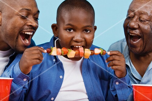 African boy eating fruit shish-kebab with father and grandfather