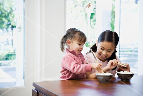 Asian sisters eating rice at table