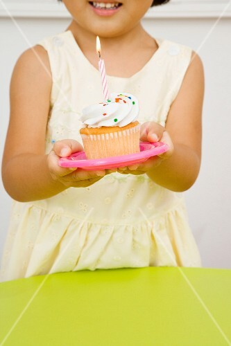Asian girl holding cupcake with candle