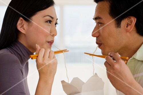 Asian couple eating noodles with chopsticks