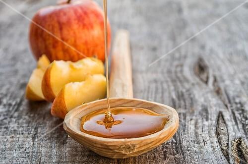 Honey falling on a wooden spoon