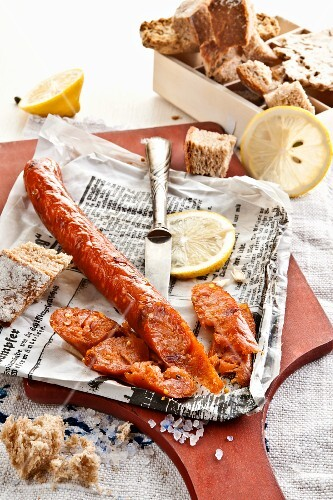 Home-made fish sausage on newspaper with lemon slices and bread