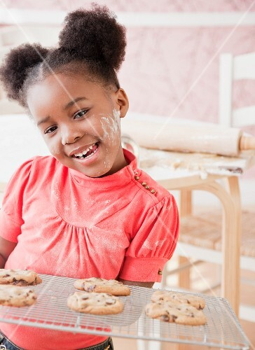African girl holding fresh baked cookies
