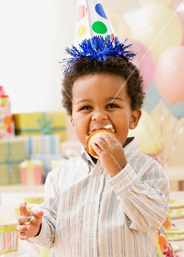 African toddler wearing party hat and eating cupcake
