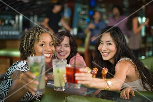 Multi-ethnic friends drinking cocktails in nightclub