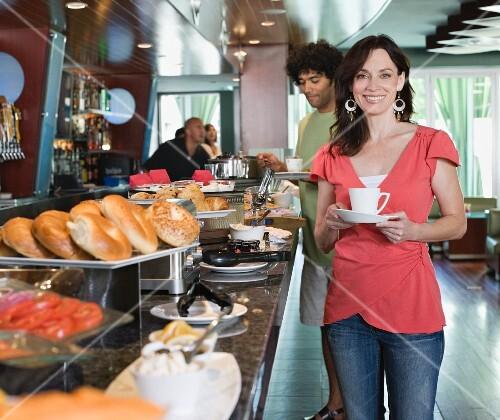 Woman holding coffee cup near breakfast buffet