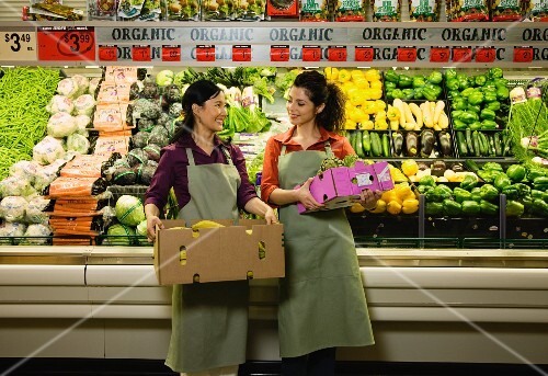 Multi-ethnic co-workers in produce section of grocery store