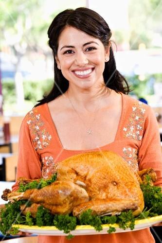 Hispanic woman serving Thanksgiving turkey