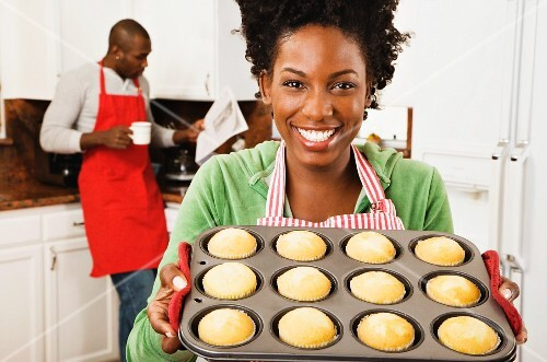African American woman holding tray of muffins