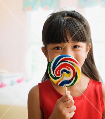 Pacific Islander girl holding lollipop
