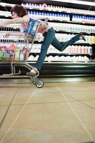 Woman riding on shopping cart