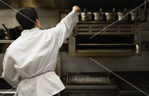 Asian male chef reaching for pot