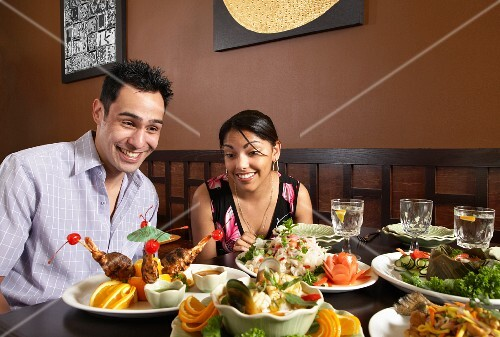 A couple in a restaurant sitting at a table laden with food