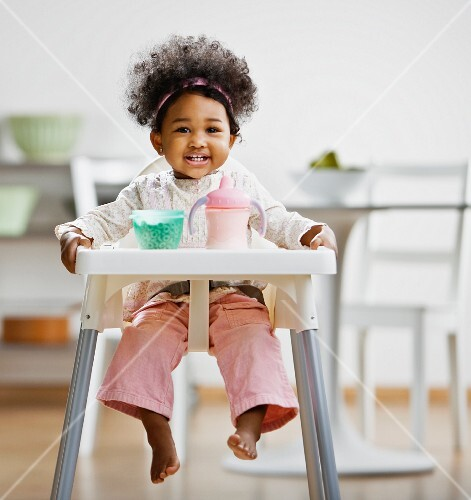 African girl sitting in high chair