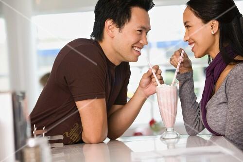 Asian couple sharing milkshake