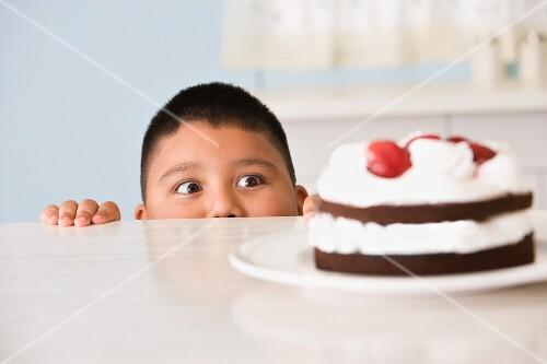 Hispanic boy looking at cake