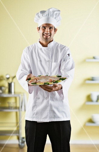 Native American male chef holding plate of food