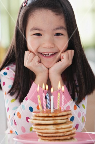 Mixed race girl with pancakes with candles
