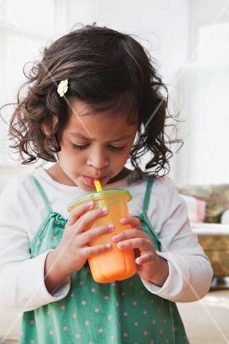Hispanic girl drinking juice