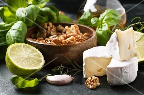 Cheese Camembert, walnuts, fresh basil and lime over dark bakground
