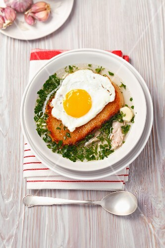 Garlic and chicken soup topped with toast and a fried egg