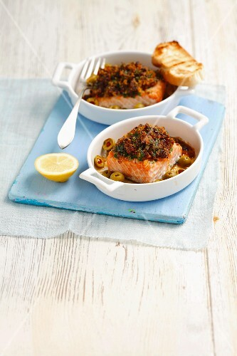 Salmon fillet with a crispy topping made from dried tomatoes, parsley and breadcrumbs, with olives and toast