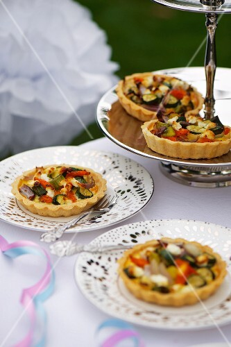 Mini vegetable quiches on a silver stand and plates