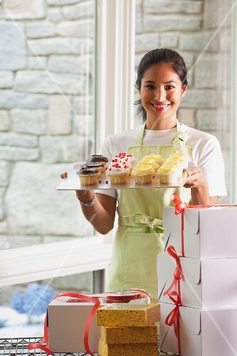 A woman packaging cupcakes