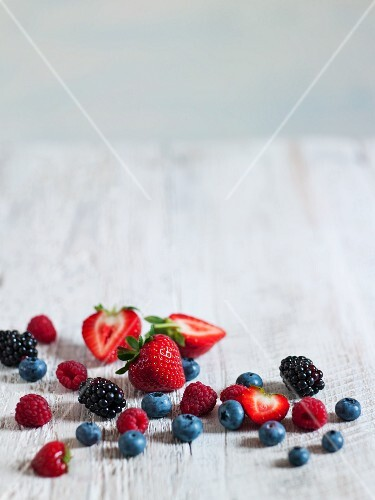Assorted fresh berries on a wooden surface