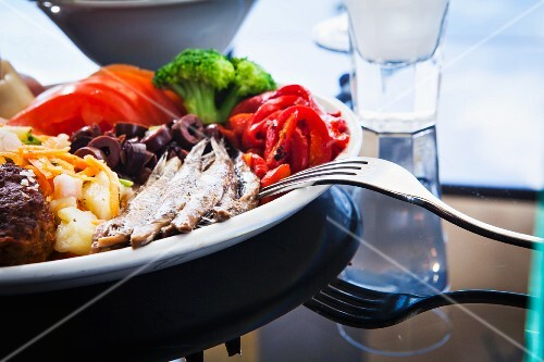 A plate of meze with anchovies, broccoli, tomatoes, peppers, potato salad, meatballs, olives and ouzo (Greece)