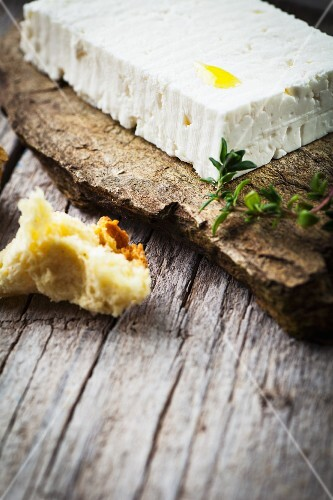 Feta on a stone slab with thyme, a chunk of bread to one side