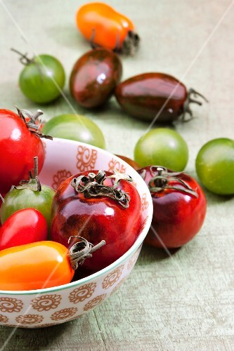 Colourful tomatoes, some in a bowl