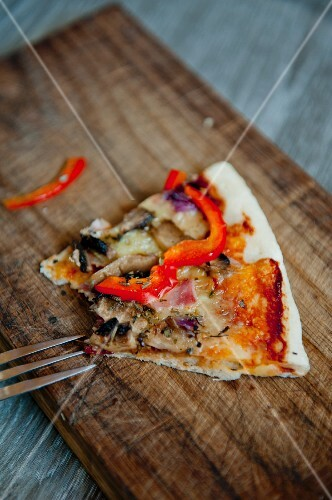 A slice of pizza with ham, mushrooms and peppers