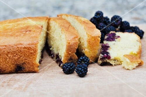 Blackberry cake, partly sliced, on a table in the garden