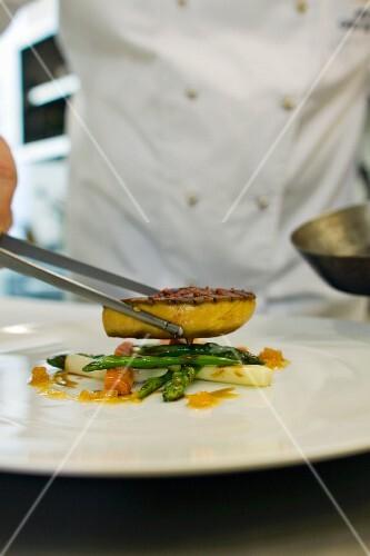 A chef serving fried foie gras on asparagus