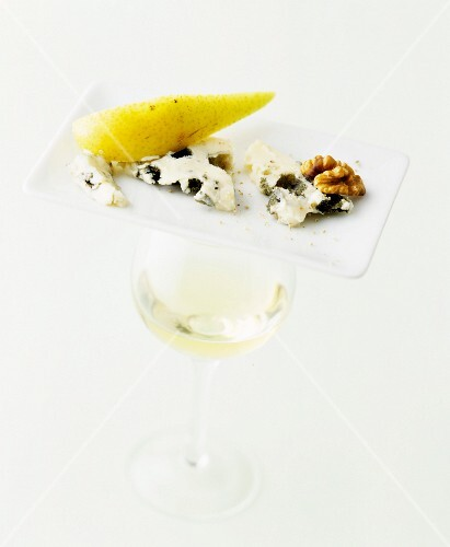 Roquefort with pear and walnut on a plate, with a glass of white wine