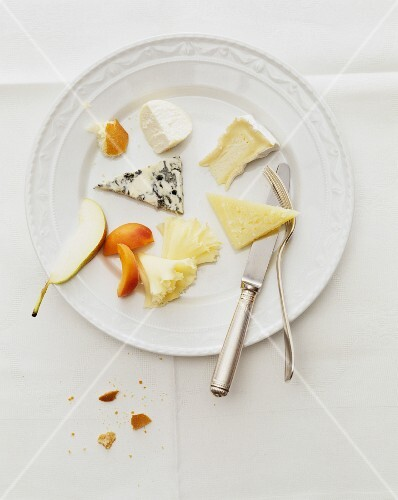 A plate of cheese with assorted varieties of cheese and fruit (view from above)