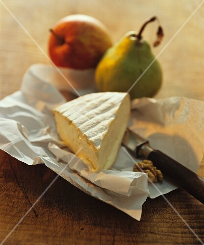A still life featuring Brie, pears and nuts