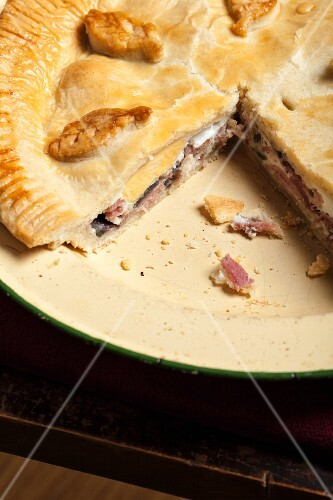 Meat pie with egg, partly sliced