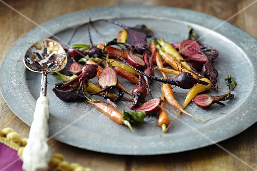 Roasted root vegetables on a plate with a spoon