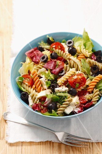 Pasta salad with olives, cherry tomatoes, iceberg lettuce and mozzarella