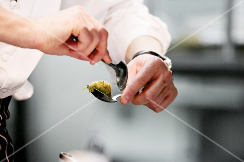 Chef shaping quenell during serice in working kitchen