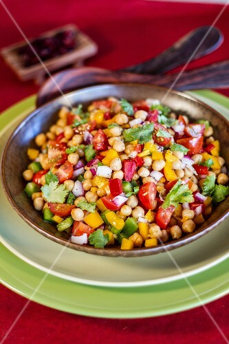 Vegan chickpea salad with tomatoes, peppers and coriander leaves