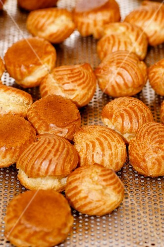 Choux pastries on a perforated metal tray