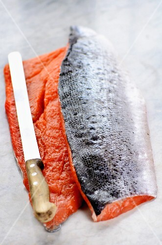 Smoked salmon fillets on a marble worktop with a knife