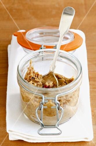 Pork rillettes in a jar on a white napkin