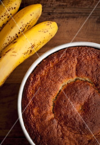 Banana cake in the baking tray with some raw bananas on the left