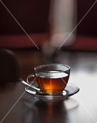Glass cup of hot tea with steam in a living room table (selective focus)
