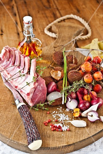Rack of lamb and ingredients for chutney on a wooden board